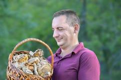 Un hombre con una cesta de setas en el bosque Fotos de archivo libres de regalías