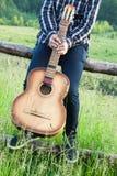 Un hombre con una guitarra en la naturaleza imágenes de archivo libres de regalías