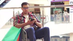 Un hombre con una incapacidad en una silla de ruedas utiliza el teléfono en la alameda después de hacer compras Cierre para arrib metrajes