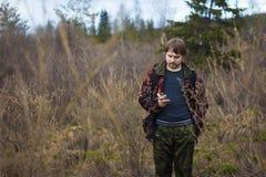 Un hombre con una mochila que se coloca en el fondo del bosque imágenes de archivo libres de regalías