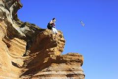 Un hombre con una mochila que se coloca encima de una montaña y que mira la gaviota del vuelo imagen de archivo libre de regalías