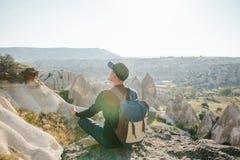 Un hombre con una mochila se sienta encima de una colina en Cappadocia en Turquía imagenes de archivo