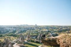 Un hombre con una mochila se sienta encima de una colina en Cappadocia en Turquía foto de archivo libre de regalías