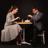 Un hombre con una muchacha juega a ajedrez y fuma un tubo en un backgr oscuro Fotos de archivo libres de regalías