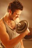 Un hombre con una pesa de gimnasia Imágenes de archivo libres de regalías