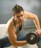 Un hombre con una pesa de gimnasia Imagen de archivo