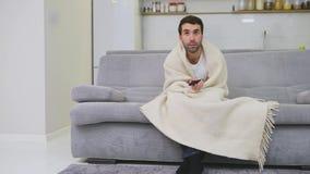 Un hombre con una sentada fría en el sofá en una manta es tan frío como sea posible Hombre enfermo del hombre en casa - Sofá gris almacen de video