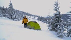 Un hombre con viajes de una mochila en las montañas del invierno almacen de video