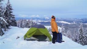 Un hombre con viajes de una mochila en las monta?as del invierno metrajes