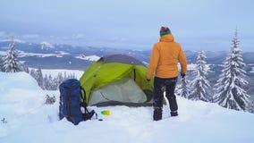 Un hombre con viajes de una mochila en las monta?as del invierno almacen de metraje de vídeo