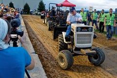 Un hombre conduce en un tirón del tractor del césped imágenes de archivo libres de regalías