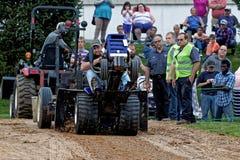 Un hombre conduce en un tirón del tractor del césped imagenes de archivo