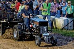Un hombre conduce en un tirón del tractor del césped fotografía de archivo libre de regalías