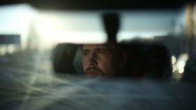 Un hombre conduce un coche Cara de la reflexión en el espejo retrovisor del coche Tiempo de la puesta del sol almacen de video