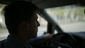 Un hombre conduce una conducción de automóviles a través de la ciudad metrajes