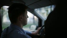 Un hombre conduce una conducción de automóviles a través de la ciudad almacen de video