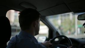 Un hombre conduce una conducción de automóviles a través de la ciudad almacen de metraje de vídeo