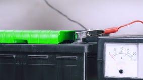 Un hombre conecta el cargador con la batería de coche metrajes
