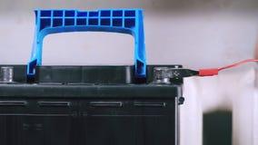 Un hombre conecta el cargador con la batería de coche almacen de metraje de vídeo