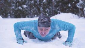 Un hombre congelado, helada-cubierto que empuja hacia arriba en nieve en un bosque del invierno metrajes