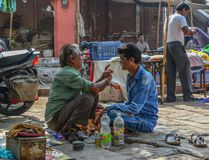 Un hombre consigue un afeitado en una peluquería de caballeros de la calle imagen de archivo libre de regalías
