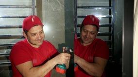 Un hombre, un constructor, en un casquillo y una camiseta rojos, aplicaciones un destornillador sin cuerda almacen de metraje de vídeo