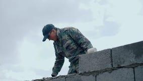 Un hombre-constructor joven pone una solución para los ladrillos metrajes
