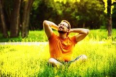 Un hombre contento sonriente feliz se está sentando en hierba verde Fotografía de archivo libre de regalías