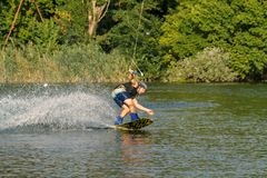 Un hombre contratado a wakeboard en el lago realiza saltos imágenes de archivo libres de regalías