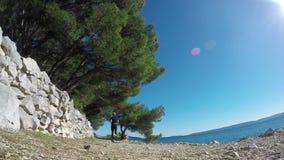 Un hombre corre con su beagle a lo largo de la costa en una cámara lenta del día claro metrajes