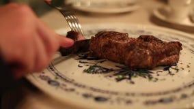Un hombre cortó la carne con un ascendente cercano de la bifurcación y del cuchillo almacen de video