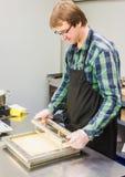 Un hombre cortó los pasteles de napoleon de la torta Imagenes de archivo