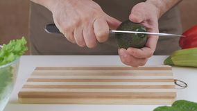 Un hombre corta con un cuchillo un aguacate en dos mitades almacen de metraje de vídeo