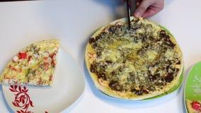 Un hombre corta la pizza con las setas con las tijeras Transfiera el pedazo del corte a otra placa almacen de metraje de vídeo