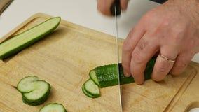 Un hombre corta los pepinos para la ensalada Chefcook está tajando el pepino de las rebanadas almacen de metraje de vídeo