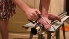 Un hombre corta una pierna del metal para la tabla metrajes