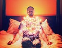un hombre cubrió en las luces de la Navidad que se sentaban en una cama que parecía presionada Imagen de archivo