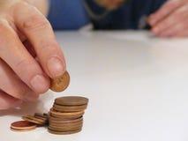 Un hombre cuenta sus peniques que hacen una pequeña pila de monedas en una tabla foto de archivo