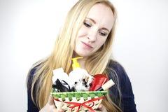 Un hombre da a muchacha hermosa un regalo - una cesta con los cosméticos y los productos de higiene Sorpresa agradable para el cu imagen de archivo