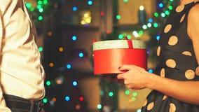 Un hombre da un regalo del Año Nuevo a una muchacha en un vestido de noche almacen de video