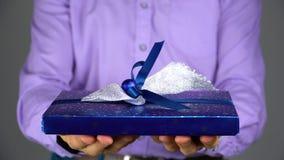 Un hombre da un regalo en una caja azul metrajes