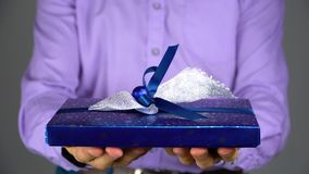 Un hombre da un regalo en una caja azul