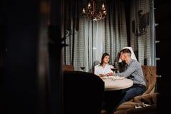 Un hombre da un regalo a su novia una fecha en un restaurante imágenes de archivo libres de regalías
