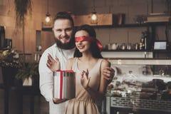 Un hombre da un regalo a una muchacha con los ojos cerrados foto de archivo