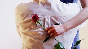 Un hombre da a una Rose roja a una mujer Ella lo abraza Fotos de archivo libres de regalías
