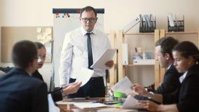 Un hombre de aspecto asiático en un traje de negocios dice a colegas del negocio sobre el trabajo hecho, recoge sus informes para metrajes