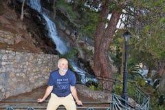 Un hombre de edad madura asiste en los carriles de la cerca de la cascada Foto de archivo libre de regalías