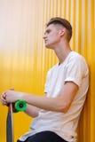 Un hombre de la juventud en una camiseta blanca con un monopatín de moda en un fondo amarillo Dinámico, reconstrucción, y concept Foto de archivo