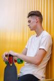 Un hombre de la juventud en una camiseta blanca con un monopatín de moda en un fondo amarillo Dinámico, reconstrucción, y concept Fotografía de archivo libre de regalías