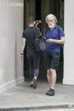 Un hombre de mediana edad canoso en los pantalones cortos que se colocan en la calle Imágenes de archivo libres de regalías
